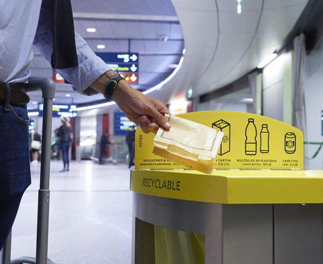 Un homme jette un sachet en papier dans une poubelle de tri sélectif dans un aéroport