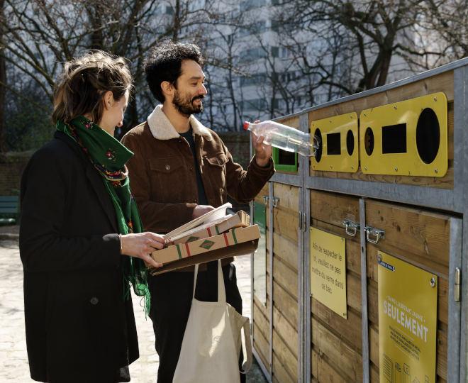 un homme et une femme jettent leurs emballages (bouteille en plastique et carton de pizza) dans un conteneur de tri sélectif